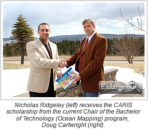 Nicholas Ridgeley (left) receives the CARIS scholarship from the current Chair of the Bachelor of Technology (Ocean Mapping) program, Doug Cartwright (right).
